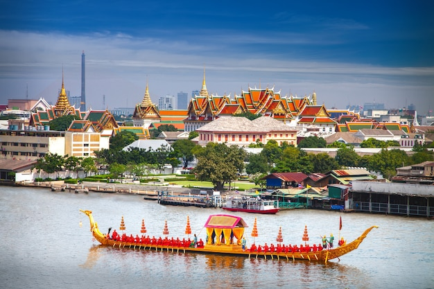 Royal boat on river with grand palace in the background of bangkok city