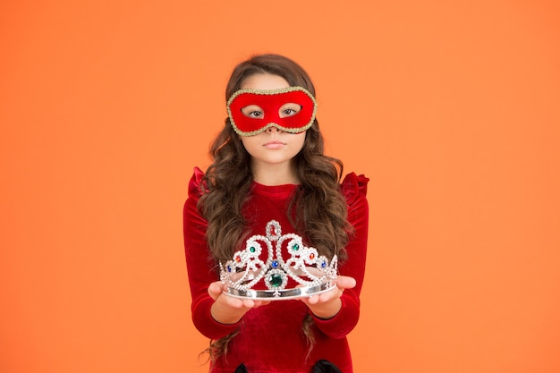 Королевское мероприятие и развлечения. награда принцессы. королевский и роскошный. посетите королевское публичное мероприятие анонимно. зимний новогодний праздник. зимний карнавал. режим инкогнито. девушка носить маску короны оранжевый фон.