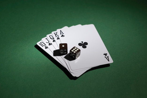 Royal flush cards with dices on green background