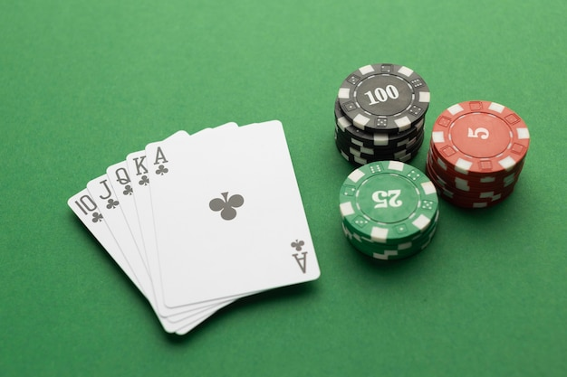 Royal flush and casino tokens on green background