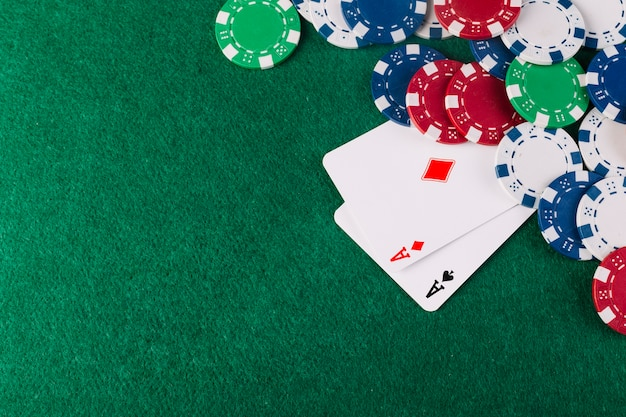 Royal flush clubs and poker chips on green background
