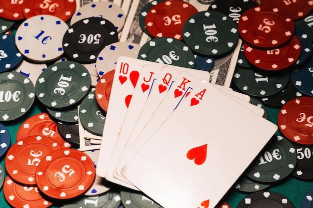 Роял флеш в покере на фоне игровых фишек и денежных долларов