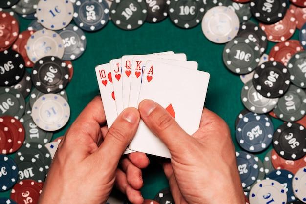 Флеш-рояль в игре в покер в руках игрока на фоне зеленого стола с игровыми фишками