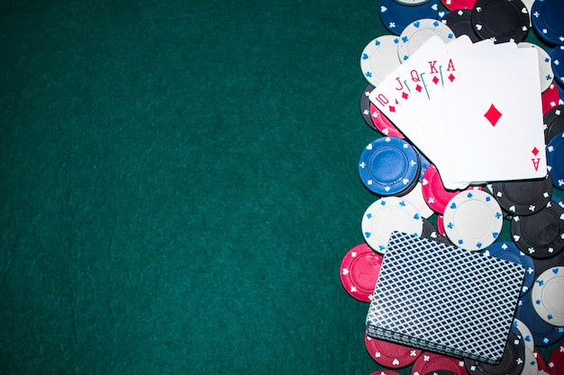 Royal flush playing card over the casino chips on green poker table