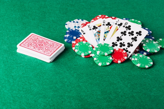 Royal flush playing card and casino chips on green poker table