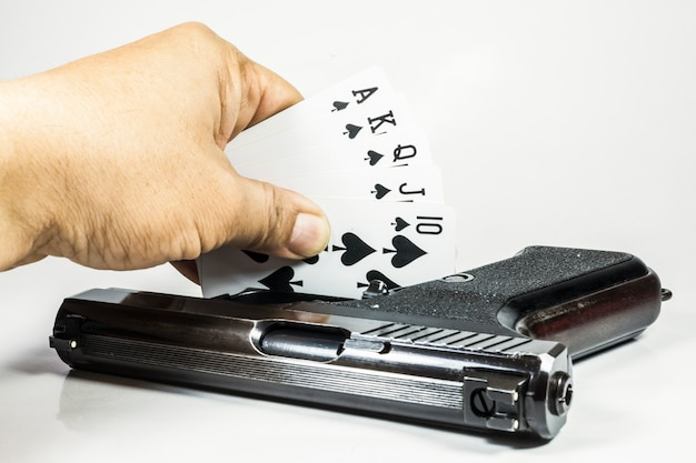 Royal flush playing cards and gun in hand on white background