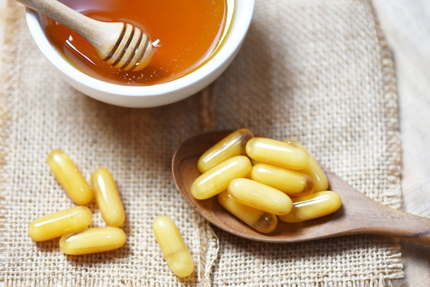 Royal jelly capsules in wooden spoon on sack  and honey in cup - yellow capsule medicine or supplementary food from nature for health