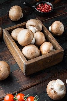 古い暗い木製のテーブルの上に、ロイヤルマッシュルームシャンピニオン全体のセット