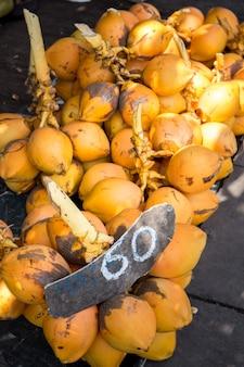 Королевские желтые кокосы на ветвях на рынке