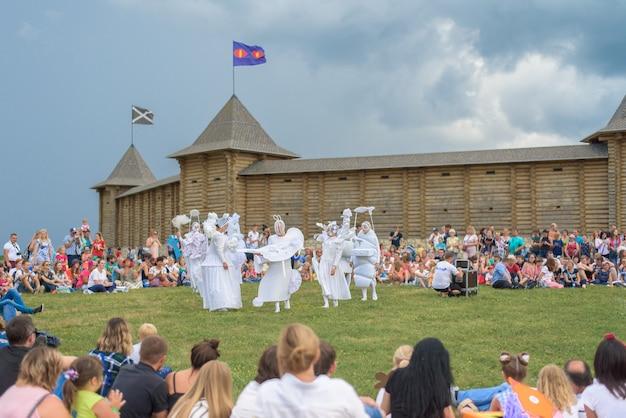 Рпарк с гуляющими людьми на фоне искусственной крепости из бревен