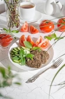 白い皿にトマトとコーヒーまたはティーカップを添えた野菜から作られた生のカツレツ