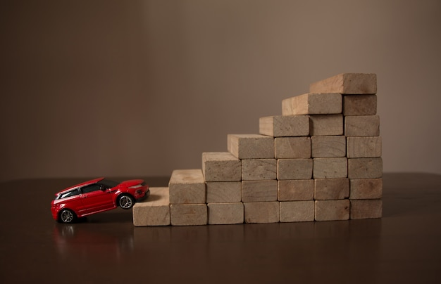 Rred going car up on roll stair step of wooden staircase stack, natural bright light background