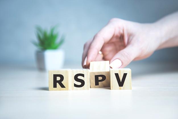여성 손으로 나무 큐브에 초대받은 사람의 응답에 대한 rsvp 약어 요청.