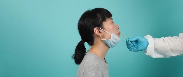 Rtpcrテスト。 covid19スワブテストの女性。流行中のコロナウイルス検査。ウイルス検査のためにサンプルを採取するメディック。青緑の背景。 ppeスーツスワブテストの博士。ウイルス迅速抗原検査。