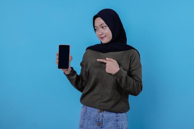 히잡을 쓴 아름다운 아시아 여성의 특성은 휴대전화를 들고 가리키며 재미있고 웃는다