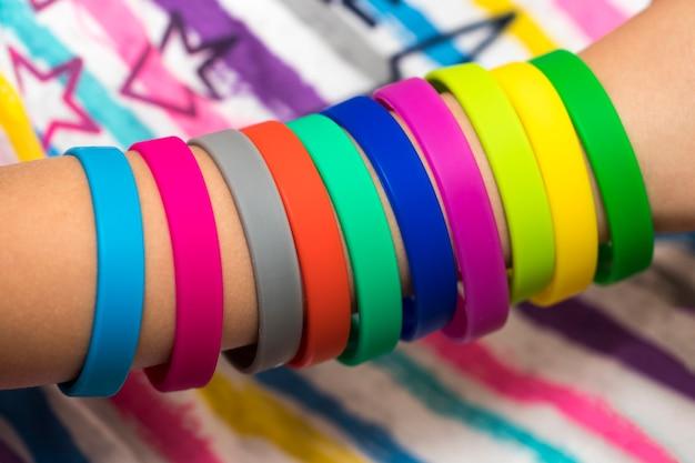 Резинки под рукой. девушки вручают браслеты из резинок. резинки цвета радуги ткацкого станка.