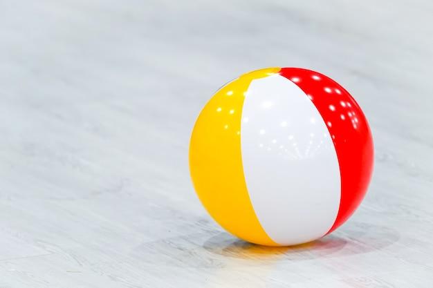 ゴム製のビーチ黄白赤のボールが灰色の木の床に横たわっていた。