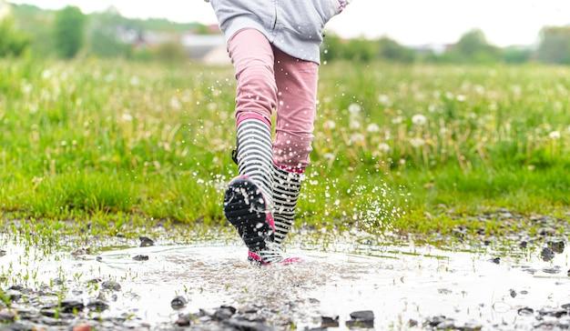 水しぶきでジャンプする過程で水たまりにゴム長靴がクローズアップ。