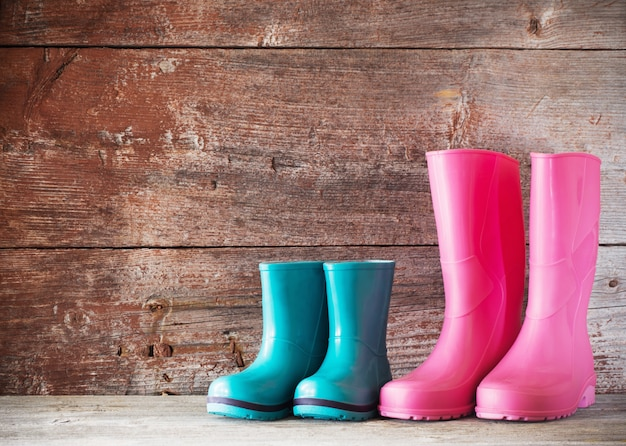 Rubber boots on old wooden wall
