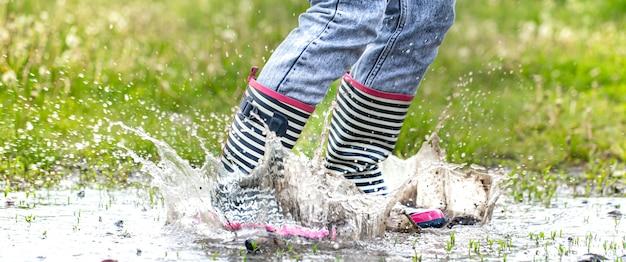 Stivali di gomma in una pozzanghera in procinto di saltare con spruzzi d'acqua