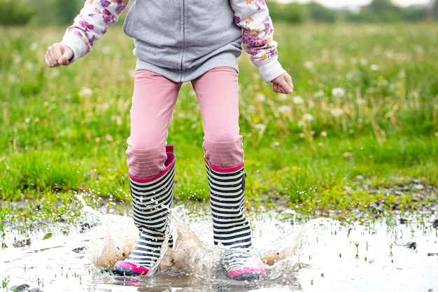 Rubber boots in a puddle in the process of jumping with splashes of water