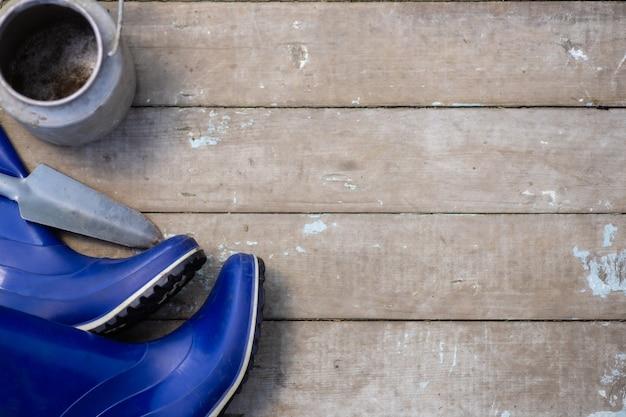 Совок резиновые сапоги и инструменты на фоне старых досок flatlay
