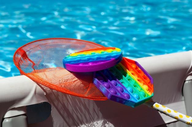 ネットのゴム製の子供のおもちゃpopitがプールの水面から捕らえられました