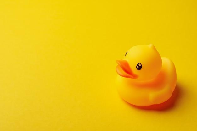 Резиновая утка на желтом фоне, место для текста