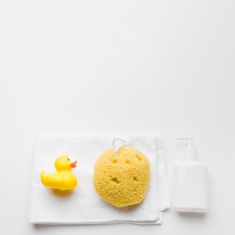 Rubber duck and sponge on towel