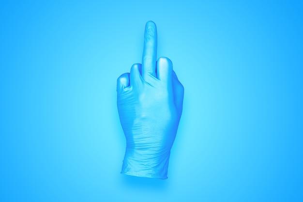 青の背景に分離された中指の手のジェスチャーをしているゴム手袋