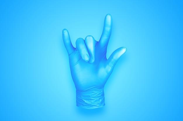 青の背景に分離されたロックハンドジェスチャーをしているゴム手袋
