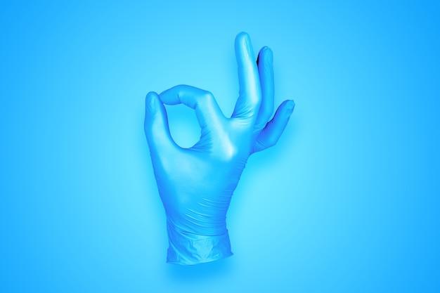青の背景に分離されたゴム手袋 ok 手ジェスチャー