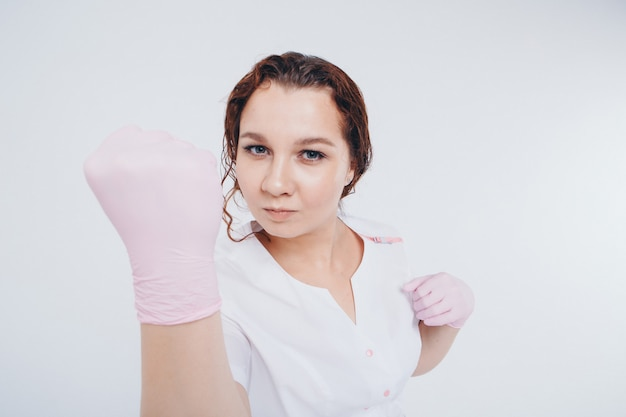 A rubber-gloved doctor threatens with his fist. a girl wears a protective gear during an epidemic. ads for antiseptics and medical equipment on a white background.