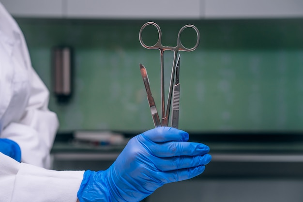 A rubber gloved hand holds two scalpels and a clamp