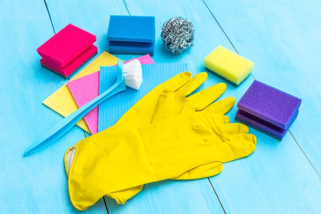 Rubber gloves, brush and cleaning cloths on a blue background.