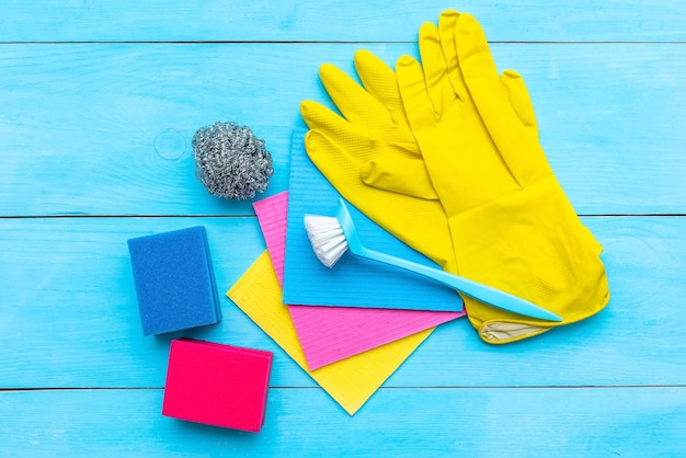 Rubber gloves, brush and cleaning cloths on blue, flat lay