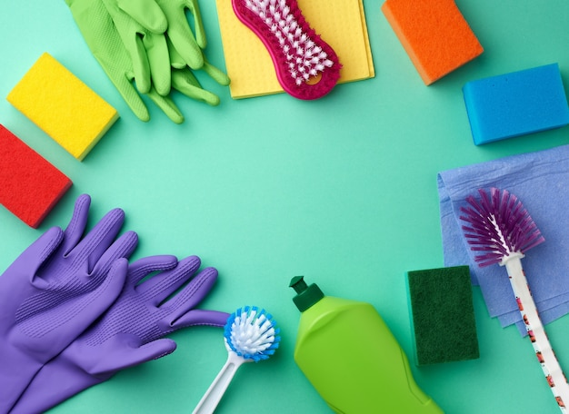 Rubber gloves for cleaning, multi-colored sponges, brushes and cleaning fluid in a green plastic bottle on a green surface