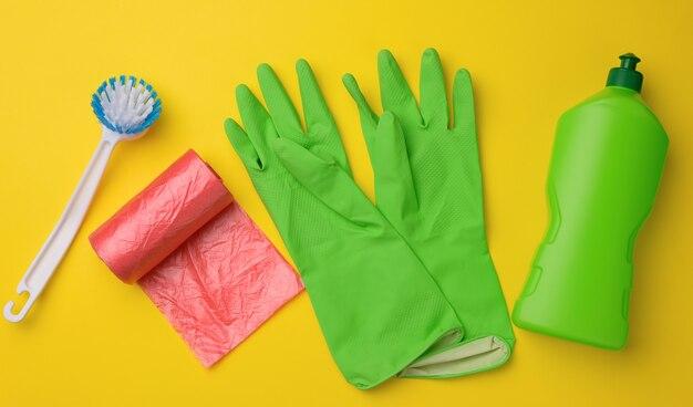 クリーニング用のゴム製の緑色の手袋、赤いゴミ箱はビニール袋のロールと黄色の背景に洗剤が入ったペットボトル、セット、上面図