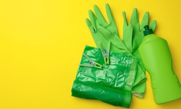 クリーニング用のゴム製の緑色の手袋、ゴミ箱のビニール袋のロールと黄色の背景に洗剤が入ったペットボトル、セット