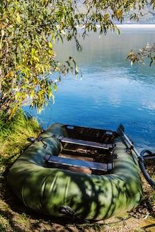 湖の木陰でゴム製のインフレータブルボート。ロシア、アルタイ、テレツコイ湖、キルサイ岬