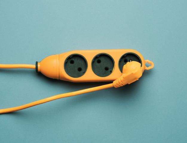 파란색 배경에 3 개의 소켓이있는 고무 오렌지 전원 스트립, 평면도