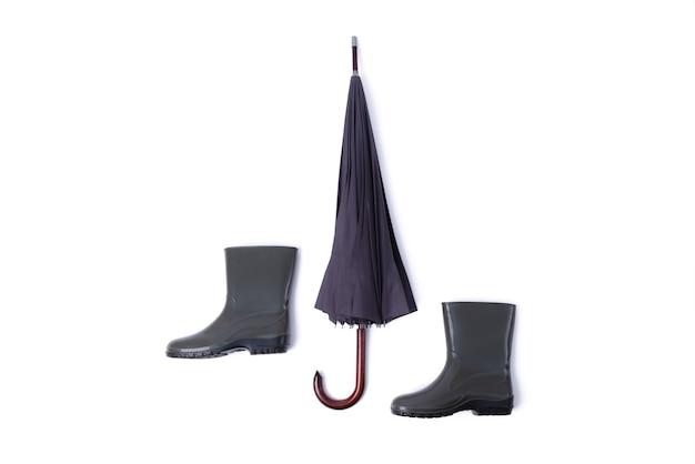 Резиновые туфли и зонтик, изолированные на белом фоне. сезон дождей и прогноз погоды. никто