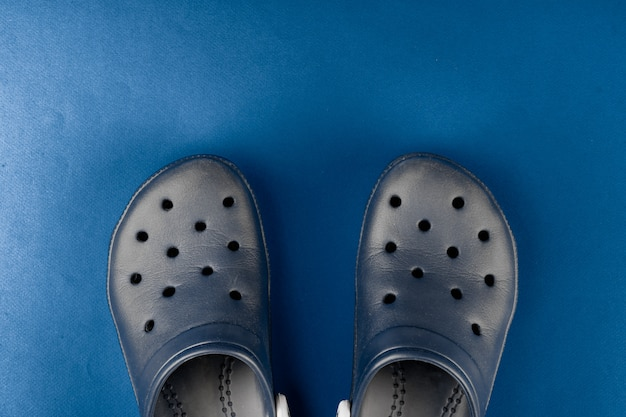 Rubber slippers on classic blue background, top view