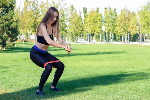 Rubber squat. fitness. athlete girl, thlete exercise at outside, woman fitness. young beautiful woman stretching in the park.