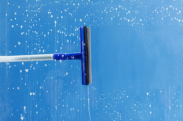 Rubber squeegee cleans window. clears a stripe of soaped window. cleaning service concept.