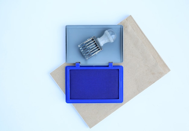 Rubber stamp and blue ink cartridges on brown book against white background.