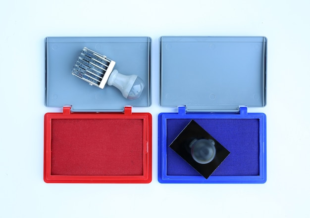 Rubber stamp and red - blue ink cartridges on white background.