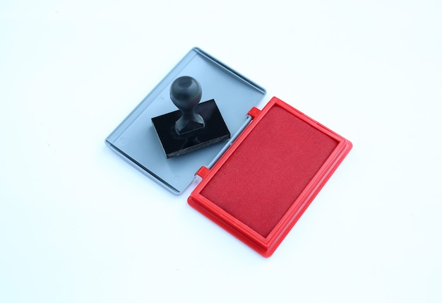 Rubber stamp and red ink cartridges on white background.