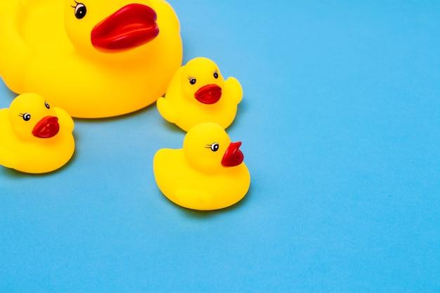 Резиновая игрушка желтого цвета мама-утка и маленькие утята на синем фоне. концепция материнской заботы и любви к детям, воспитание и образование детей