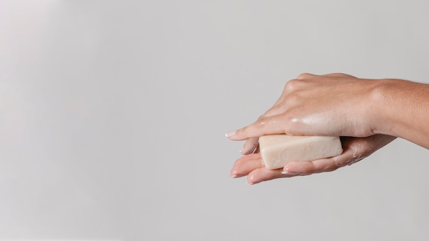 Rubbing hands with block of soap copy space side view